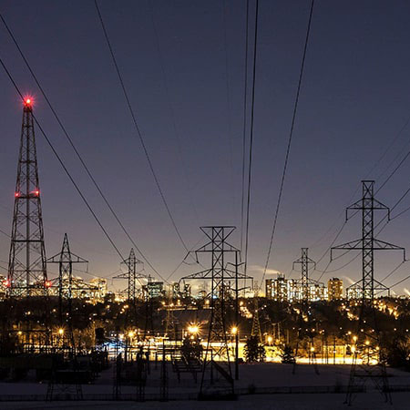 Electricity towers at night with city light up in background