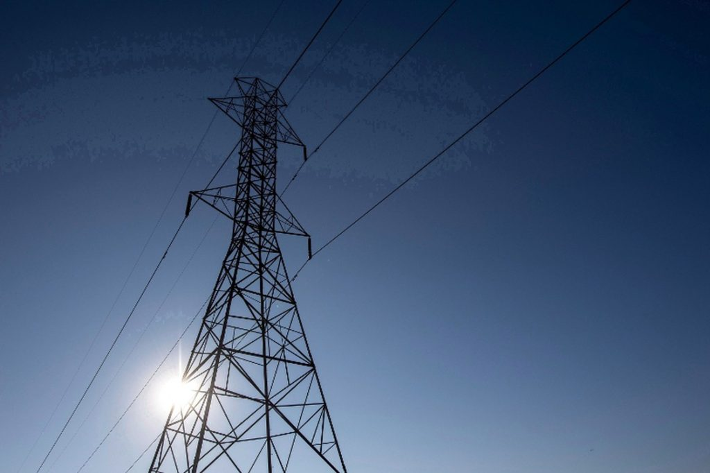 Hydro line with a blue sky and sun in the background