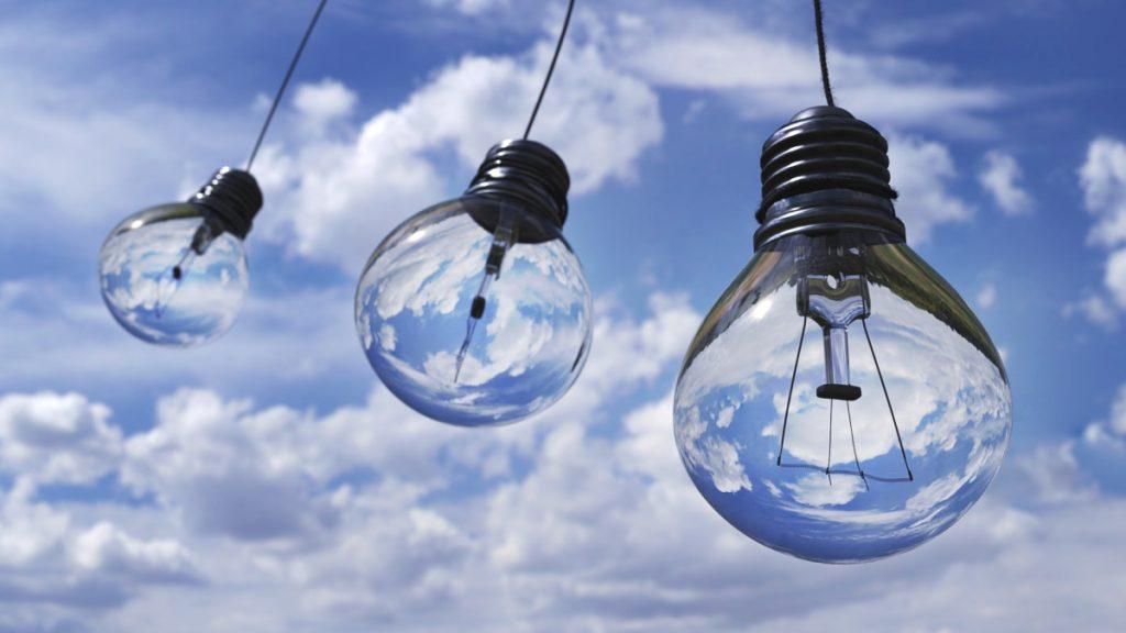 Light bulbs against a blue sky with clouds